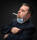 Man in medical mask with a thermometer — Stock Photo