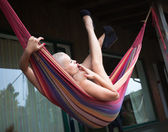 Nude woman with cigarette resting in a hammock — Stok fotoğraf