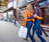 Man and woman walking down the street hugging — Stock Photo