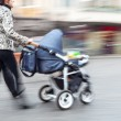Young family with small children and a pram walking down the str — Stock Photo #38566601