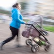 Mother with small children and a pram walking down the street — Stock Photo #38566607