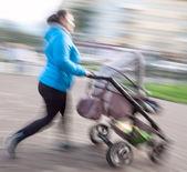 Mère avec enfants en bas âge et un landau marchant dans la rue — Photo