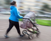 Mother with small children and a pram walking down the street — Stockfoto
