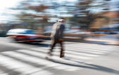 An elderly man crosses the street in a crosswalk — ストック写真