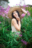 Girl in straw hat against nature and old wall background — Stock Photo