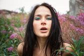 Seminude beautiful girl among the flowers — Stock Photo