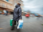 Woman in a jacket with shopping plastic bags — Stock Photo