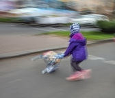 Little girl with toy stroller crossing the road — Stock Photo
