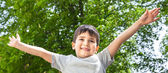 Boy with his hands up smiling — Stockfoto