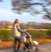 Mother with small child and a pram walking down the street — Stock Photo