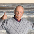 Senior man enjoying the outdoors with wavy sea — Stock Photo #47386897