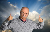 Senior man with glasses enjoying the outdoors with cloudy sky — Stock Photo