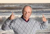 Senior man enjoying the outdoors with wavy sea — Stock Photo