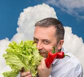 Man holding lettuce against the blue sky — Stock Photo
