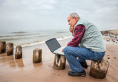 Thoughtful elderly man with the laptop — Stock Photo