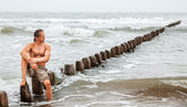 Middle-aged man sitting near the sea — Stock Photo