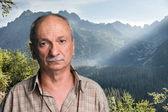Senior man on top of a mountain — Stock Photo