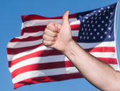 Tumb up sign against of USA flag — Stock Photo