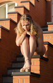 Young beautiful naked woman sunbathing on the stairs — Stock Photo