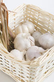 Garlic with dried lemon grass inside a rattan basket — Stock Photo