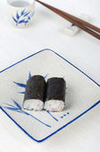 Sushi on a plate with chopstick and tea cup — Stock Photo