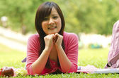 A shot of an asian student studying on campus lawn — Stock Photo