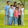 Extended family standing outdoors smiling — Stock Photo