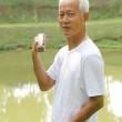 Senior man using dumbells on outdoor - Stock Photo