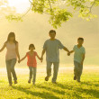 Stock Photo: An asian family walking in the park during a beautiful sunrise,