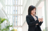 Asian business girl using phone — Stock Photo