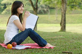 Asian college girl sitting — Stock Photo