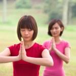 Asian girls performing yoga outdoor — Stock Photo