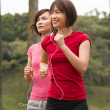 Asian girls jogging outdoor while listening to music — Stock Photo #19206449