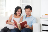 Asian chinese pregnant couple reading — Stockfoto