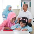 Stock Photo: Indonesimalay family doing homework together, quality time