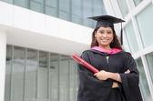 Joven diplomado mujer india con fondo de campus — Foto de Stock