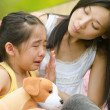 Stock Photo: Asichinese girl crying while being comfort by her mother, outdoor background