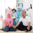 Malaysian family celebrating while watching television over a to — Foto Stock