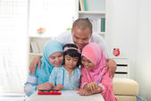 Malaysian family doing homework together — Stock Photo
