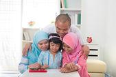 Malaysian family doing homework together — Stock Photo