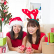 Asian girls during christmas celebration with home background — Stock Photo #23379094