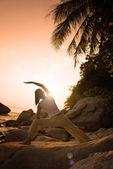 Stranden yoga, silhuetten av en kvinna som utför krigare pose — Stockfoto