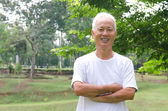 Chinese asian senior male outdoor with green background — Stock Photo