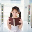 Smart looking little chinese school girl read at the library — 图库照片
