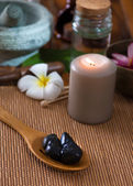 Hot stone massage with spa treatment items on the background — Stock Photo