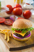 Hamburger fast food with plenty of raw materials on the backgrou — Stock Photo