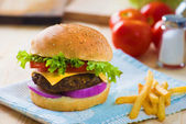 Cheese burger , french fries and fast food with plenty of raw ma — Stock Photo