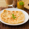 Roti canai and teh tarik, very famous drink and food in malaysia — Stock Photo #24770093
