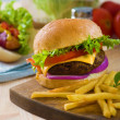 Stock Photo: Burger and french fries with fast food ingredients on the backgr