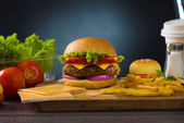 Cheese burger with plenty of fast foods ingredients on the backg — Stock Photo